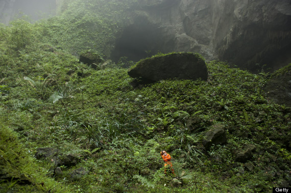 A Hang Son Doong explorer navigates an plant-covered cavescape.
