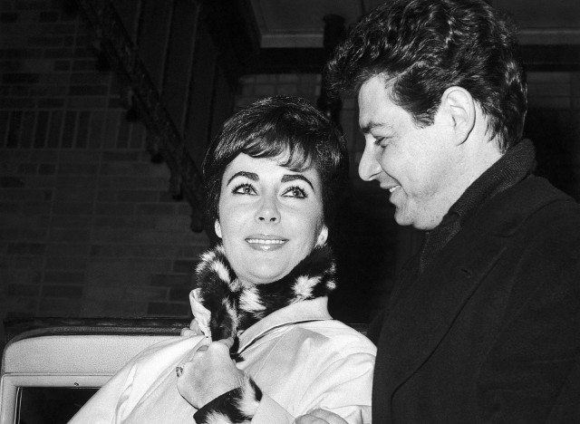 British actress Elizabeth Taylor is helped by her husband American singer Eddie Fisher, as she leaves Presbyterian hospital in New York, United States on Dec. 13, 1959, following a bout with double pneumonia. She rode from her room in a wheelchair but walked out with her husband's help. They went to their suite in the Waldorf-Astoria Hotel. The actress entered the hospital on Nov. 26, 1959. (AP Photo)
