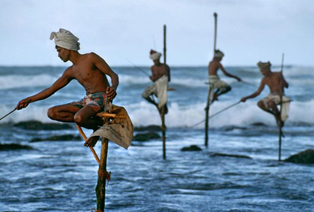 "Weligama, South coast, Sri Lanka, 1995.""Fishermen along the southern coast of Sri Lanka cast their lines in the traditional way atop poles so they can work in shallow water without disturbing the fish.""  - George Eastman HouseThe theatrical stage would not offer a finer gesture, nor a more equisite doubling between the near and the far, than does this picture.  McCurry captures the beauty of a cultural tradition and with it a natural choreography.  This image also preserves a practice now essentially lost to technology, having all but disappeared in the intervening years since the photograph was made.  -Anthony Bannon Magnum Photos, NYC5948; MCS1995006K200, Phaidon, 55, South Southeast, Iconic Images, final book_iconic"