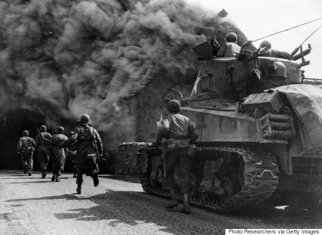 """Soldiers of the 55th Armored Infantry Battalion and tank of the 22nd Tank Battalion move through smoke filled street. Wernberg, Germany."" Pvt. Joseph Scrippens, April 22, 1945."